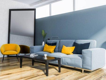 Foto de Esquina de un moderno salón interior con paredes azules, un suelo de madera y un sofá azul cerca de una mesa de café. maqueta de representación 3d - Imagen libre de derechos