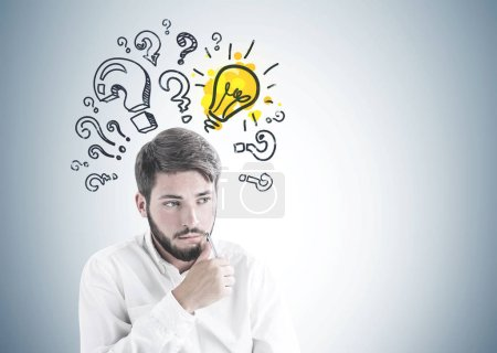 Troubled young bearded caucasian businessman in white shirt sitting with pen near his face and thinking looking sideways. A gray wall background with question marks and a yellow light bulb. Mock up