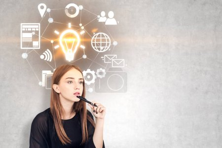 Photo for Pensive young woman with long fair hair holding a pen near her chin. A concrete wall background with glowing light bulb and business icons. Mock up - Royalty Free Image