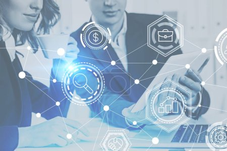 Two unrecognizable business people, man and woman, working together in office. Glowing network icons Immersive interface foreground Toned image double exposure mock up