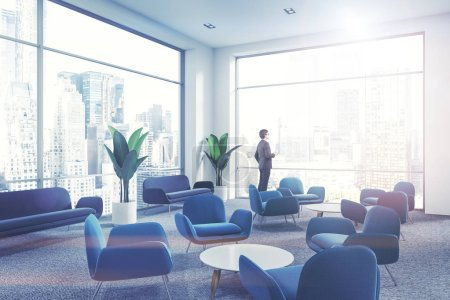 Businessman with coffee in modern company waiting room interior with soft blue armchairs standing next to round coffee tables on a gray carpet. 3d rendering mock up toned image