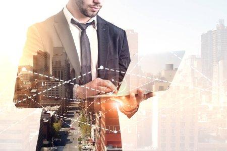 Photo pour Homme d'affaires barbu méconnaissable en costume et cravate tenant son ordinateur portable debout contre des graphiques sur le paysage urbain du matin. Bourse et concept de fintech. Image tonique double exposition espace de copie - image libre de droit