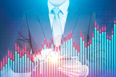 Unrecognizable businessman in a suit and a tie working with a tablet computer. Glowing graphs foreground and blue background. Stock exchange and hi tech concept. Toned image double exposure