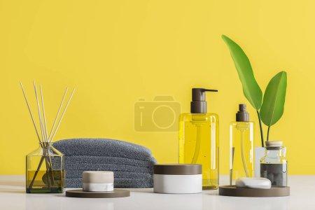 Photo pour Bouteilles transparentes avec savon et spa produits en blanc simulé des conteneurs. Bâtons d'arôme et pile de serviettes gris sur tableau blanc. Fond de mur jaune. Relaxation et soins auto concept. rendu 3D - image libre de droit
