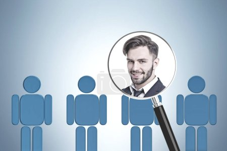 Photo for Portrait of smiling young businessman in magnifying glass over row of blue human figures in gray room. HR concept. - Royalty Free Image