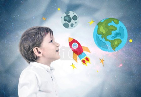 Side view of an adorable little caucasian boy with blond hair wearing white shirt and dark blue jeans and looking upwards. Colorful rocket, moon and earth sketch. Dream big concept double exposure