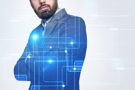 Unrecognizable bearded businessman standing with crossed arms in a white room with graphs holograms and hud. Hi tech concept. Toned image double exposure copy space film effect