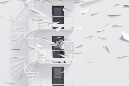 Young businessman with crossbow shooting paper planes standing on white building emergency stairs. Achieving your business goal concept. Toned image