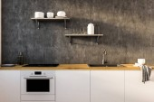 Gray and white kitchen interior with white and wooden countertops, an oven and a sink. Shelves on the wall. 3d rendering