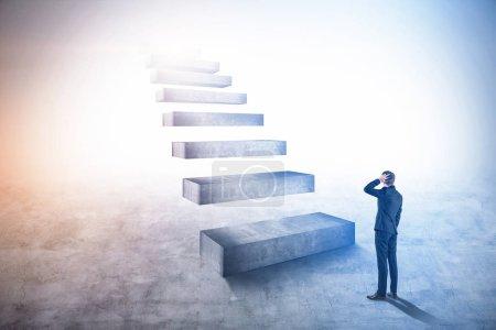 Foto de Joven hombre de negocios rascándose la cabeza mirando una escalera de carrera gigante. Estilo de vida empresarial y concepto de liderazgo. Espacio de copia de imagen tonificada - Imagen libre de derechos