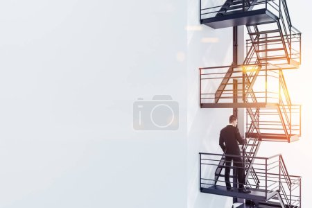 Young businessman with smartphone standing on white building emergency stairs. Having a plan b concept. Toned image copy space