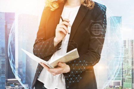 Photo for Unrecognizable businesswoman standing with her planner against morning cityscape. Earth hologram. Toned image double exposure. Elements of this image furnished by NASA - Royalty Free Image