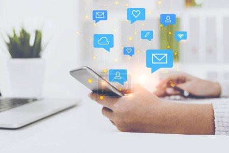 Foto de Mano de mujer en Jersey blanco con smartphone sentado en la mesa de la oficina. Los medios sociales de azul y los iconos de red de computación en la nube. Doble exposición - Imagen libre de derechos