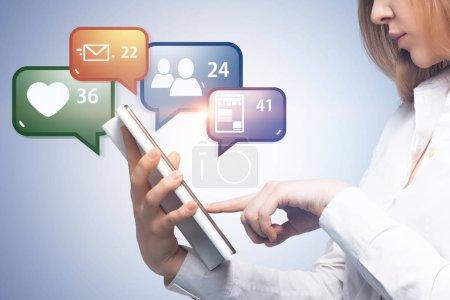 Foto de Vista lateral de empresaria irreconocible con su tablet PC. Colores medios sociales las notificaciones y los iconos. Fondo azul. Concepto de la vida de internet - Imagen libre de derechos