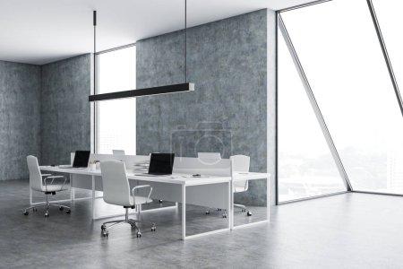 Photo pour Grunge espace ouvert Bureau intérieur avec des murs en béton et plancher, loft windows, quatre tables d'ordinateur portables et chaises blanches. rendu 3D - image libre de droit
