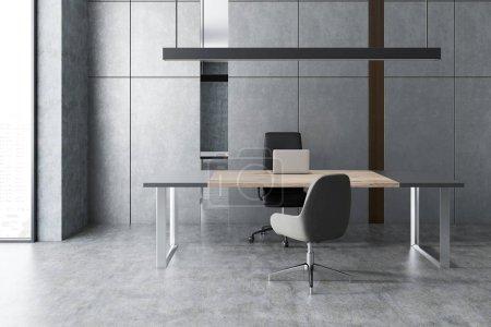 Photo pour Gestionnaire minimaliste intérieur de bureau avec murs gris et plancher, fenêtre loft, grande table grise et en bois avec ordinateur portable et chaise visiteur. Concept d'entreprise de marketing. Rendu 3d - image libre de droit