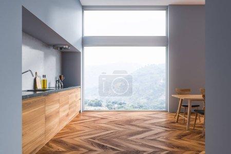 Photo pour Intérieur de cuisine moderne avec des murs gris, plancher en bois, comptoirs en gris et en bois, une table avec chaises et fenêtre du grenier. rendu 3D - image libre de droit