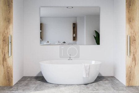 Modern bathroom interior with white walls, concrete floor, white bathtub with large mirror hanging above it. 3d rendering