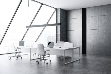 Open space office interior with gray walls and floor, loft windows, four computer tables with laptops and white chairs. 3d rendering