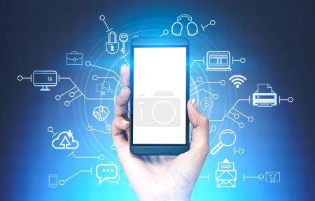 Photo pour Main de femme tenant smartphone avec maquettes écran sur fond bleu foncé avec des icônes ordinateur et internet et interface de hud. Image tonique - image libre de droit