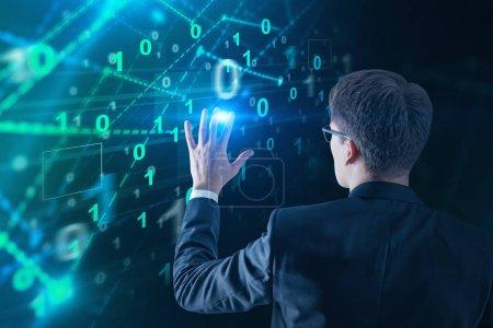Photo pour Vue arrière de l'homme d'affaires dans des verres à l'aide de chiffres binaires interface. Salut concept technologie. Double exposition image tonique - image libre de droit