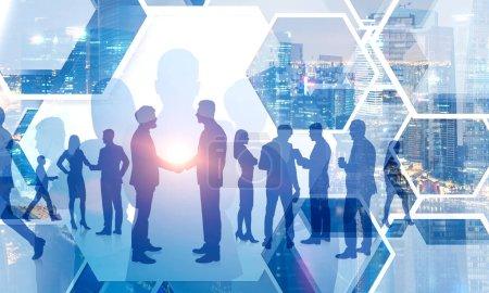 Foto de Siluetas de gente de negocios dándose la mano y caminando sobre el fondo del paisaje urbano. Concepto de sociedad. Imagen tonificada doble exposición - Imagen libre de derechos