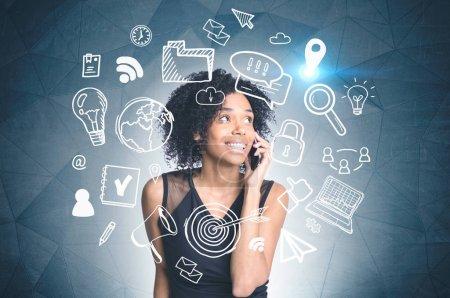 Photo pour Femme afro-américaine souriante parlant au téléphone debout près du mur gris foncé avec ordinateur blanc et dessin sur Internet. Image tonique double exposition - image libre de droit
