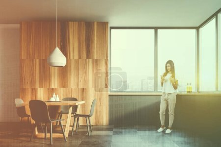 Photo for Woman in white and wooden kitchen interior with tiled floor, large window, gray countertops and wooden table with gray chairs. Toned image double exposure - Royalty Free Image