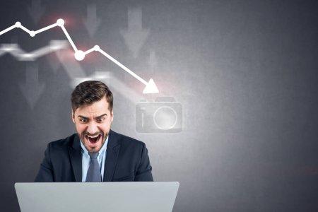 Photo pour A souligné homme barbu regardant ordinateur portable et des cris. Chute de graphique dessiné sur le mur de béton derrière lui. Maquette - image libre de droit