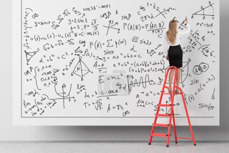 Photo for Rear view of blonde woman standing on ladder and writing formulas on white wall. Concept of woman in science - Royalty Free Image
