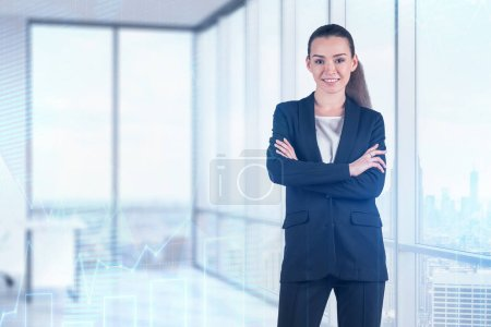 Photo for Smiling young businesswoman in dark suit standing with crossed arms in panoramic office with double exposure of graphs. Toned image - Royalty Free Image