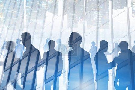 Photo pour Silhouettes des membres de l'équipe entreprise diversifiée travaillant ensemble et en communiquant sur fond de gratte-ciel avec cityscape reflétant en elle. Double exposition image tonique - image libre de droit