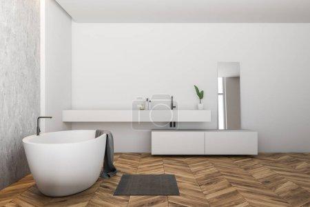 Photo pour Vue de côté de la salle de bains moderne avec des murs blancs et béton, plancher en bois, baignoire blanche avec serviette sur elle et évier blanc avec miroir. rendu 3D - image libre de droit