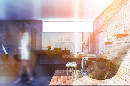 Photo pour Femme à l'intérieur de l'élégante salle de bains avec des murs en béton et en bois, baignoire noir, debout noir lavabo sur comptoir noir et deux toilettes. Tonique de flou de l'image - image libre de droit