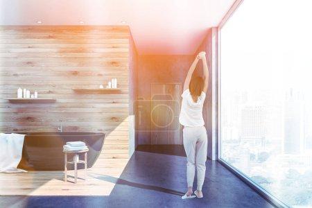 Photo pour Femme dans l'intérieur de la salle de bain panoramique avec des murs en béton et en bois, plancher de béton, baignoire noir avec une serviette blanche dessus et étagères avec les shampoings et crèmes au-dessus d'elle. Image tonique - image libre de droit