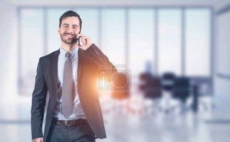 Photo pour Joyeux jeune homme d'affaires avec barbe en costume sombre parlant sur smartphone debout dans la salle de réunion de bureau floue. Concept de style de vie d'affaires. Image tonique - image libre de droit