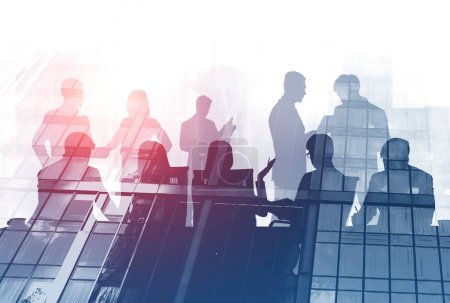 Photo for Silhouettes of business people sitting at meeting room table with their colleagues discussing work over gray skyscraper background. Double exposure toned image - Royalty Free Image