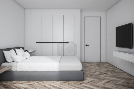 Photo for Side view of master bedroom with white walls, wooden floor, gray bed with TV set in front of it and white. Narrow door with handle. 3d rendering - Royalty Free Image