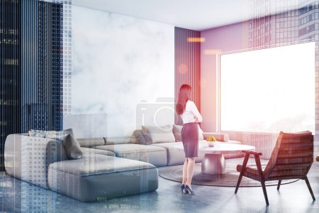 Photo for Young woman in formal clothes standing in modern living room with white and marble walls, soft beige sofa and armchair near round coffee table. Toned image double exposure of city - Royalty Free Image