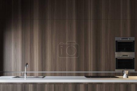 Photo pour Intérieur de cuisine avec des armoires en bois foncés avec construit dans des fours et des comptoirs en bois foncés avec construit dans l'évier et la cuisinière. rendu 3D - image libre de droit