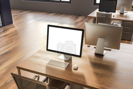 Photo pour Écran d'ordinateur avec maquettes écran se tenant debout sur table de bureau en bois dans la salle avec des murs gris et plancher en bois. Concept de publicité. rendu 3D - image libre de droit
