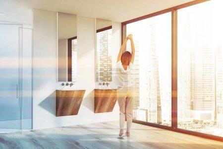 Photo pour Jeune femme en pyjama debout dans la salle de bain moderne avec murs blancs, sol en bois, deux lavabos en bois et douche avec portes vitrées. Image tonique - image libre de droit