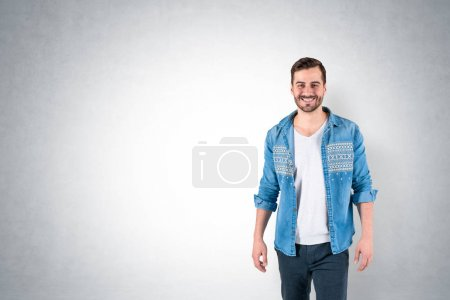Photo for Portrait of handsome young man with beard wearing casual clothes and smiling standing near concrete wall. Concept of positive emotions. Mock up - Royalty Free Image