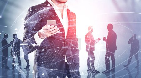 Photo for Man in suit holding smartphone standing over blurred background with business people silhouettes and double exposure global digital network hologram. Concept of technology in business. Toned image - Royalty Free Image