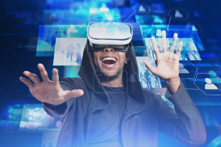 Photo for Excited young man in casual clothes experience virtual reality gesturing in VR headset and having fun. Toned image double exposure. Elements of this image furnished by NASA - Royalty Free Image