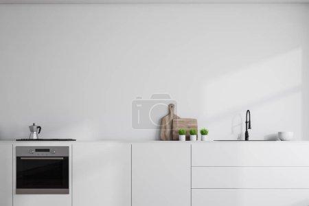 Photo pour Fermez-vous vers le haut des partie supérieure du comptoir blanc avec construit dans l'évier, la cuisinière et le four restant dans l'intérieur moderne de cuisine avec les murs blancs. Rendu 3d - image libre de droit