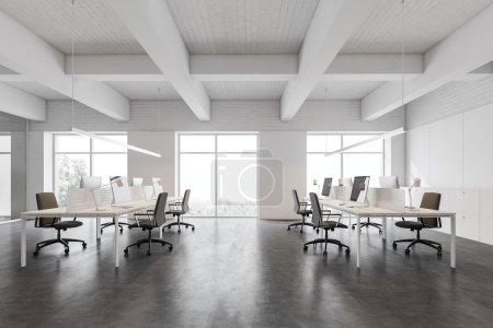 Photo pour Intérieur du bureau moderne à aire ouverte avec murs blancs et briques, sol en béton, grandes fenêtres et rangées de tables d'ordinateur blanches avec chaises noires. Rendu 3d - image libre de droit