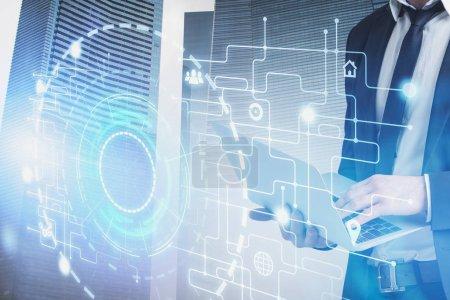 Foto de Hombre de negocios que utiliza el ordenador portátil en la ciudad con doble exposición de la interfaz Hud y los iconos de Internet. Concepto de alta tecnología y ciudad inteligente. Imagen tonizada - Imagen libre de derechos