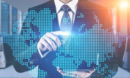 Photo pour Homme d'affaires utilisant un ordinateur tablette dans un bureau flou avec hologramme de carte du monde. Concept de commerce international et de haute technologie. Image tonique double exposition - image libre de droit