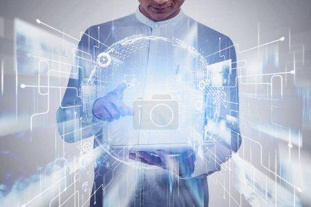 Foto de Hombre irreconocible usando tablet computer con doble exposición al holograma del planeta y la interfaz de red. Concepto de redes sociales e imagen tonificada. - Imagen libre de derechos